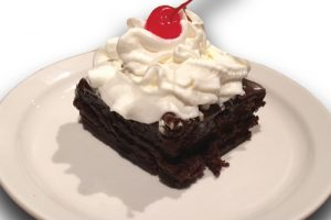 brownie with whipped cream on a plate