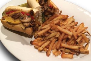 cheese steak sandwich and fries on a plate
