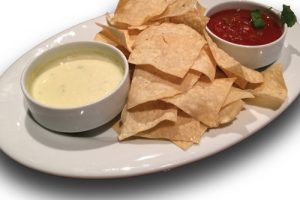 Queso chips and cheese on a plate